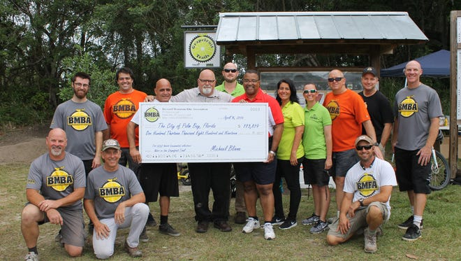 Palm Bay Mayor William Capote accepts a ceremonial check representing the 5,000+ volunteer hours the Brevard Mountain Bike Association spent maintaining the Grapefruit Trails in Palm Bay in 2015.