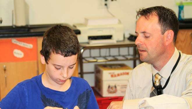 Wayne Davis, left, is assisted by student teacher Adam Kindl. Kindl is doing his student teaching in Renee Kenner's sixth-grade science class. Kenner challenged Kindl to come up with a modern experiment to spark her students' interest in science.