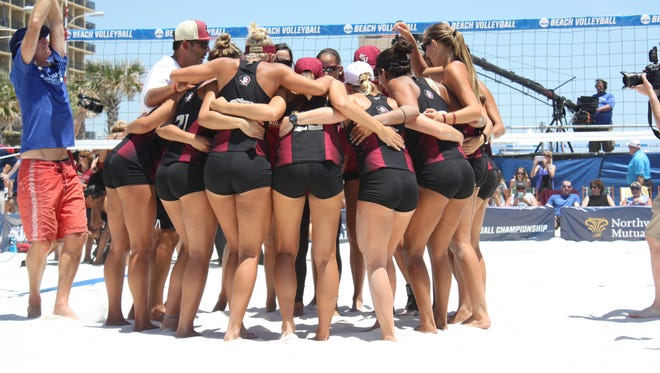 The FSU Beach Volleyball team huddles together before their duel against USC for the national championship.
