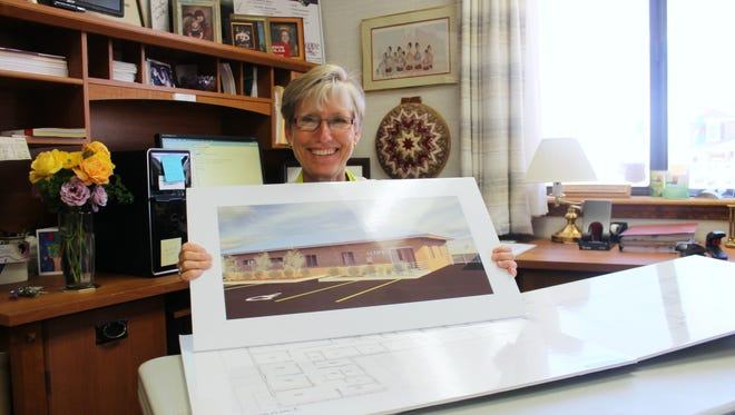 COPE Executive Director Kay Gomolak holds an illustration of what the new COPE building will look like when construction is complete.