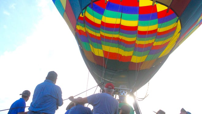 Crews get a hot air balloon prepared for flight at the Red River Balloon Rally.