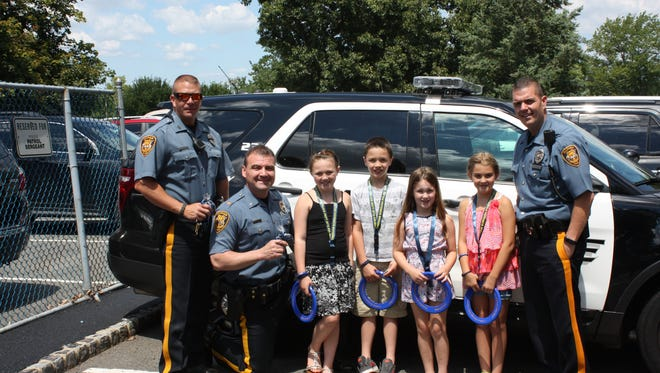 Traffic Safety Officer Roy George, Chief Philip Crosson Jr. and Community Services Officer Brian Colatrella thank kids Amber Reilly, Hunter Reilly, Abigail Cornine, Victoria DeCorso for donating handmade bracelets.