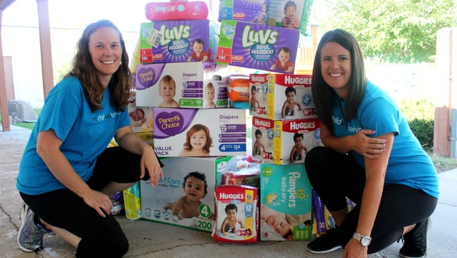 Carrie Chalverus and Vera Ulibarri, event coordinators of No Child Wet Behind, deliver 30,000 diapers and a check for $4,500 to the Pregnancy Help Center on Thursday morning.