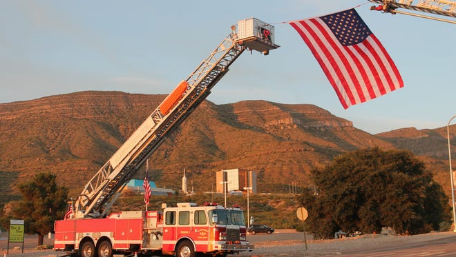 In this file photo Alamogordo Firefighters display an American flag from two apparatuses.