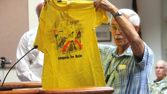 John Douglass, original organizer of Kids Kingdom, holds up a shirt from the community's fundraising efforts in the 90s.