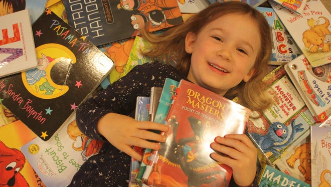 Four-year-old Sasha Kenlon takes a break from reading and relaxes with a few of her favorite books.