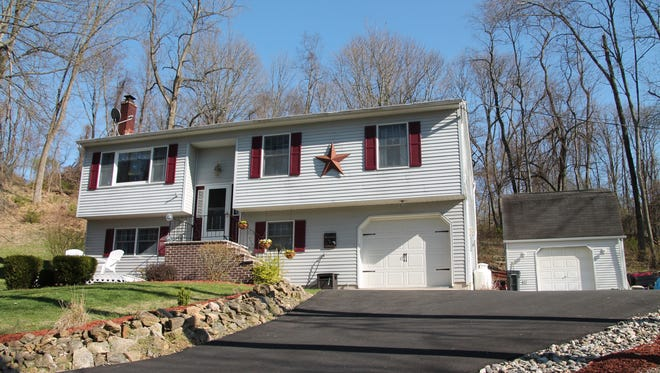 This four-bedroom bilevel has an updated kitchen and a sun room with a wrap-around deck.