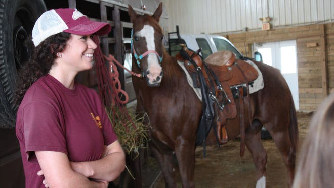 Jessica Buckman smiles as she teaches a group of students of the importance of horse safety.