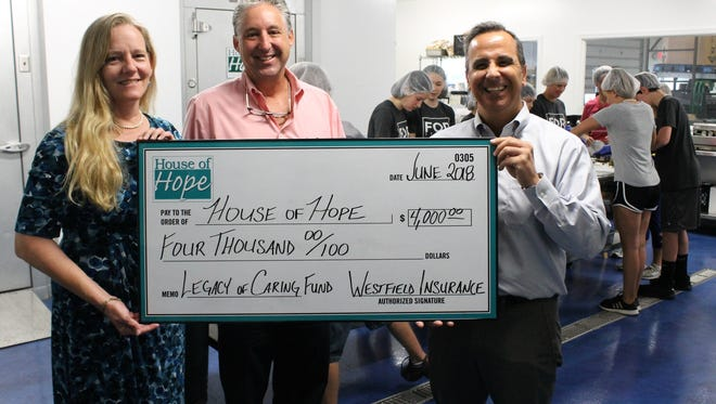 Stuart Insurance's Margaret Kiess and Cabot Lord present Westfield's Legacy of Caring Fund grant award to House of Hope's Rob Ranieri while touring the Elisabeth Lahti Nutrition Center.