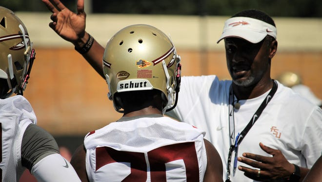 FSU head coach Willie Taggart talks with WR Keyshawn Helton during the third practice of fall camp