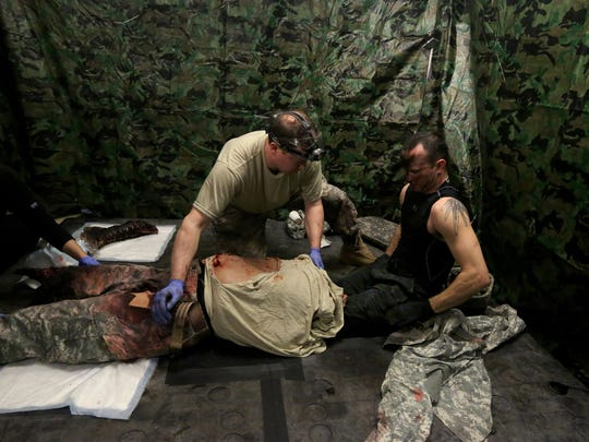 Jordan Gonzalez, right, climbs out of a simulated torso and legs used at the University of Washington Medical Center to create battlefield situations that are more real than just working with a mannequin. At left is Vanessa Ortiz and holding the torso is Troy Reihsen.
