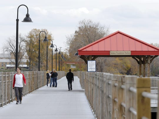 Pedestrians use the Fox Cities Trestle Trail bridge on a late October afternoon. The bridge was the site of a mass shooting six months ago.