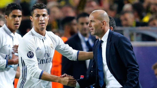 Real Madrid's Cristiano Ronaldo celebrates scoring the opening goal with Real Madrid's manager Zinedine Zidane.