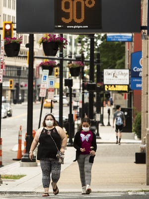 Pedestrians pass through the downtown area on Wednesday as temperatures hovered in the 90s.