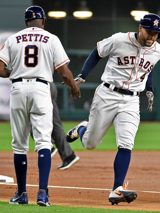 Houston Astros' George Springer (4) shakes the hand of third base coach Gary Pettis after hitting a solo home run off Texas Rangers starting pitcher Nick Martinez during the first inning of a baseball game, Tuesday, June 13, 2017, in Houston. (AP Photo/Eric Christian Smith)