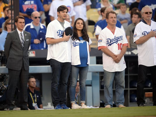 Ashton Kutcher and Mila Kunis line up for the national anthem before Game 4 of the 2016 NLCS playoff baseball series between the Chicago Cubs and the Los Angeles Dodgers at Dodger Stadium on Oct. 19, 2016, in Los Angeles.