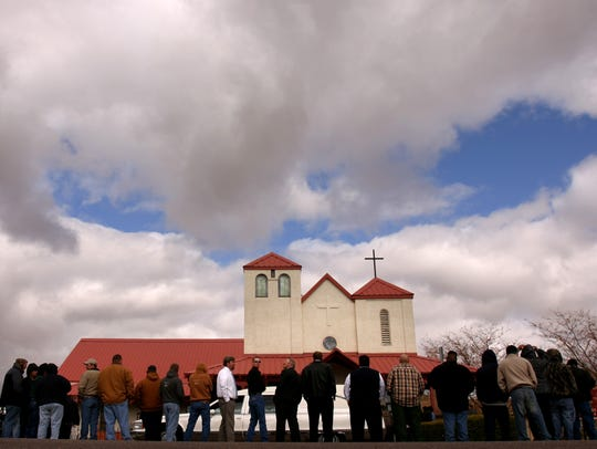 Attendees of Vincent Romero's funeral service stand