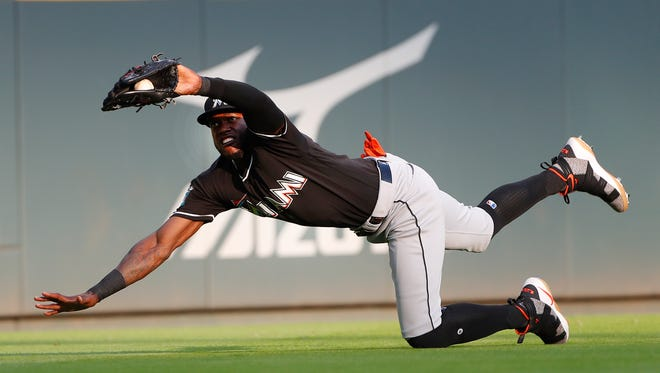 Miami Marlins left fielder Cameron Maybin makes a diving catch against the Atlanta Braves on Saturday, May 19, 2018, in Atlanta.
