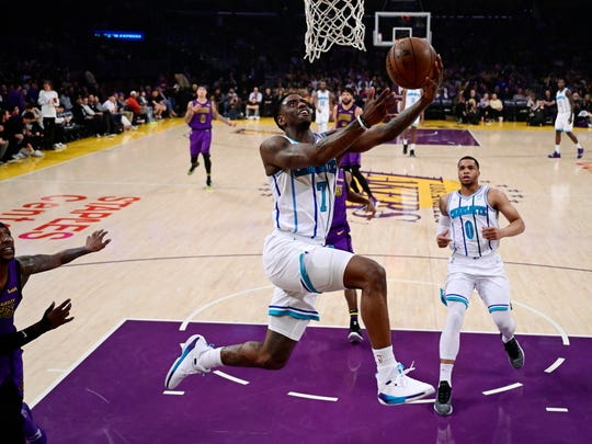 Charlotte Hornets guard Dwayne Bacon, center, shoots as Los Angeles Lakers guard Kentavious Caldwell-Pope, left, and Hornets forward Miles Bridges watch during the first half of an NBA basketball game Friday, March 29, 2019, in Los Angeles. (AP Photo/Mark J. Terrill)