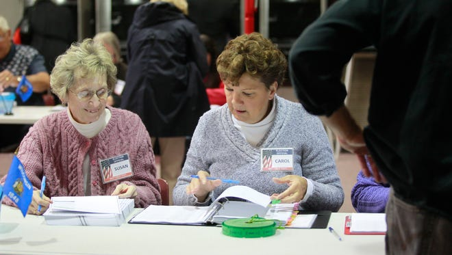Poll workers at the Brookfield Public Safety Building check names of voters.
