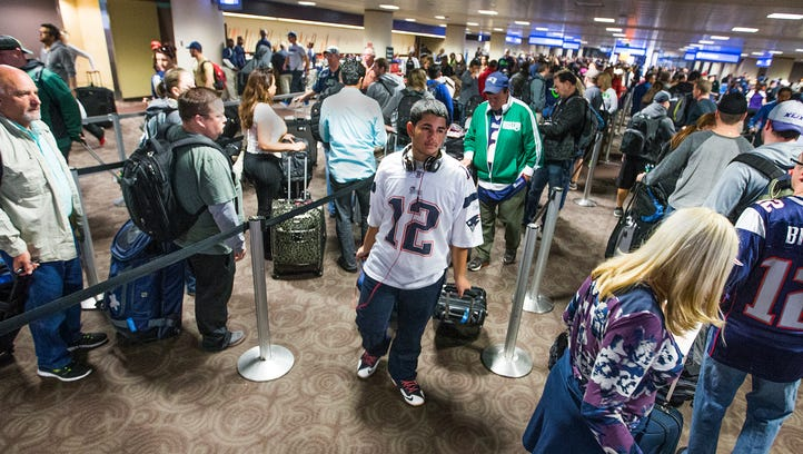 Travelers pass through Sky Harbor International Airport the day after the NFL Super Bowl XLIX football game between the New England Patriots and the Seattle Seahawks, Monday.