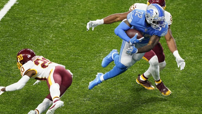 Detroit Lions running back D'Andre Swift (32) avoids a tackle by Washington Football Team cornerback Jimmy Moreland (20) and inside linebacker Jon Bostic (53) before falling into the end zone for a touchdown during the second half of an NFL football game, Sunday, Nov. 15, 2020, in Detroit.