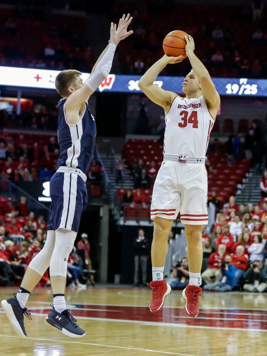 Wisconsin's Brad Davison (34) shoots a three-point basket against Yale's Noah Yates (4) during the second half of an NCAA college basketball game Sunday, Nov. 12, 2017, in Madison, Wis. Wisconsin won 89-61. (AP Photo/Andy Manis)
