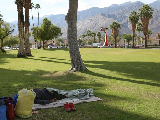 A homeless person sleeps on the ground in Sunrise Park in Palm Springs, December 1, 2016.