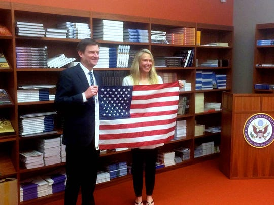 Vanessa O'Brien at the United States Embassy in Islamabad, Pakistan with Ambassador David Hale holding the American flag she took to the summit of K2.