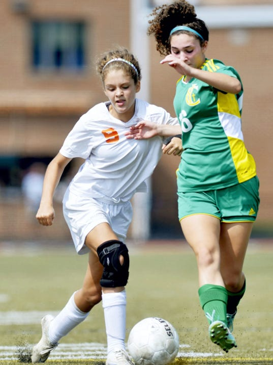 York Suburban's Roma Williams and York Catholic's Nicole Chiaverini fight for possession in the second half of the championship game at the York Suburban Soccer Tournament Saturday. York Suburban won, 2-1, to win the title.