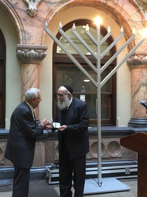 Rochester Deputy Mayor R. Carlos Carballada, left, and Rabbi Nechemia Vogel, director of Chabad Lubavitch of Rochester, at a ceremony Friday to light a menorah in the City Hall Atrium.