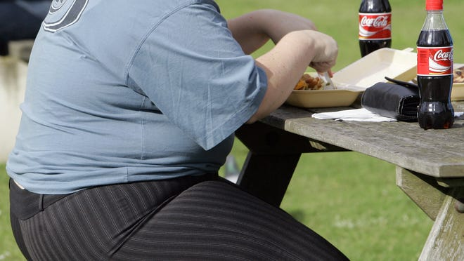 An overweight person eats in London in October 2007.  Almost a third of the world population is now fat, and no country has been able to curb obesity rates in the last three decades, according to a global analysis released May 29, 2014.