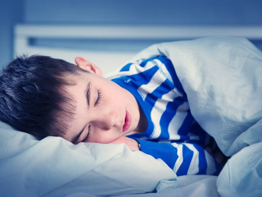 Boy sleeping in bed in pajamas