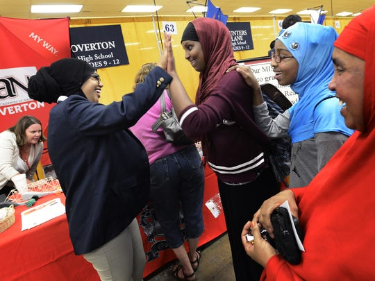 Ruwayda Mahamoud, center, with her sister, Elwaad, and their mother, Ken Hersi, right, high-fives Overton High School senior Simale Abadula while talking about attending the high school next year during the First Choice Festival at the state fairgrounds in Nashville on Monday, Sept. 23, 2013.