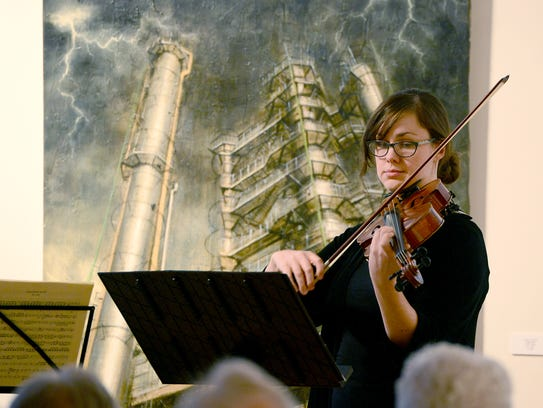 Kara Poorbaugh plays the viola in front of a painting