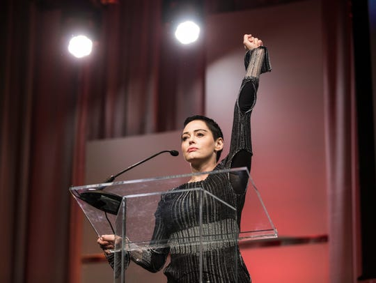 Rose McGowan raises her fist as she speaks during The