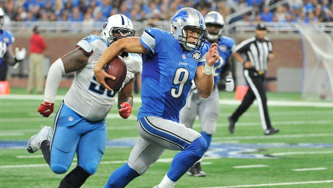 Lions quarterback Matthew Stafford runs away from the Titans' DaQuan Jones for a first down in the third quarter Sunday.