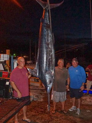 The crew of Third Day, from left, Glenn Leon Guerrero, Richard Santos and Chris Duenas, hauled in a 330-pound marlin on the first day of the 20th Annual Guam FishermenÕs Cooperative Association Guam Marianas International Fishing Derby on Saturday, Aug. 1, 2015.