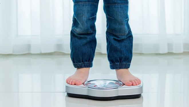 Child measures weight on a weight scale.