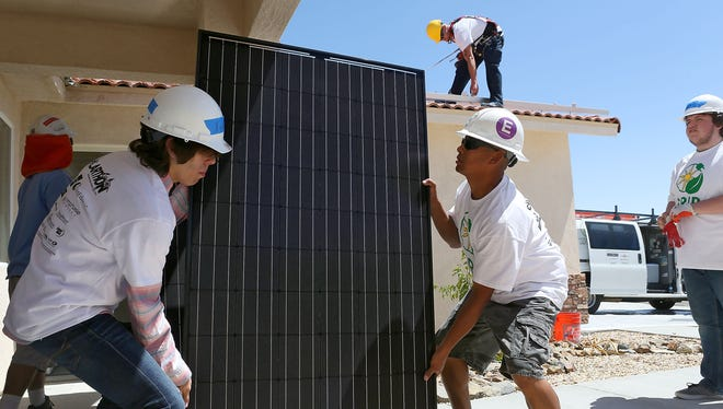 Xavier Villegas of Desert Hot Springs High School's Renewable Energy Academy of Learning, left, and Alberto Panuco of Hot Purple Energy, lift a solar panel for installation at a low-income Desert Hot Springs home on April 9, 2015. The project was part of GRID Alternatives' Solarthon.