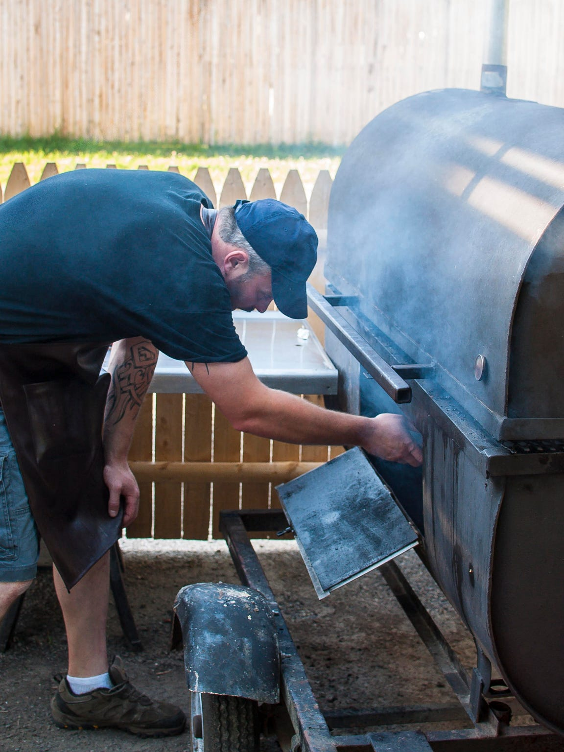 """Trevor Leroux, self-described """"pig-roaster extraordinaire"""", feeds wood into the smoker Roaster's BBQ in Milton on Monday, July 11, 2016."""