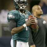 Former Eagles quarterback Michael Vick warm ups before a game against Dallas last season. Vick reveres Philadelphia for giving him a second chance in the NFL.
