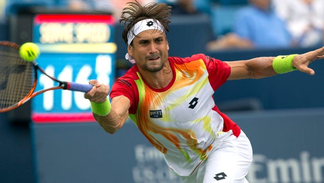 David Ferrer returns a shot against Julien Benneteau on day six of the Western & Southern Open tennis tournament at Linder Family Tennis Center.