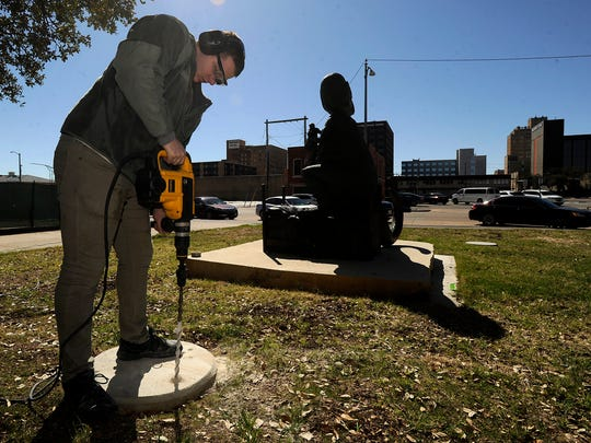 Dyess We Care Team member Jordan Collins drills a hole in a base for one of the sculptures for the Adamson-Spalding Storybook Garden being built on the on the southeast lawn of the Abilene Convention Center on Saturday, Feb. 25, 2017.