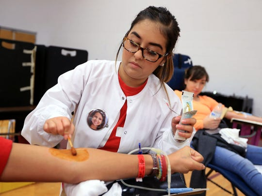 Wearing a button with the face of eight-year-old Hilari DeLeon, Meagan Salinas, a phlebotomist with the Coastal Bend Blood Center, to start a blood draw on a donor on Wednesday, October 26, 2016 at Sinton High School.