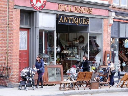 Pedestrians pass Dickinson's Antiques on Main Street