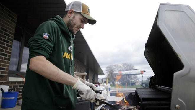 Ryan Reiser, head cook at American Legion Post 38 in Grand Chute, prepares brats for a fundraiser last year. Post 38 recently paid its $103,300 road assessment in full.