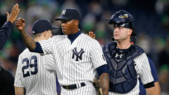 Teammates congratulate New York Yankees relief pitcher Aroldis Chapman, center, after Chapman, the first player disciplined under Major League Baseball's new domestic violence policy, closed out the Yankees 6-3 victory in a baseball game against the Kansas City Royals at Yankee Stadium in New York, Monday, May 9, 2016. New York Yankees catcher Brian McCann, right, hit a first inning solo home run in the game.