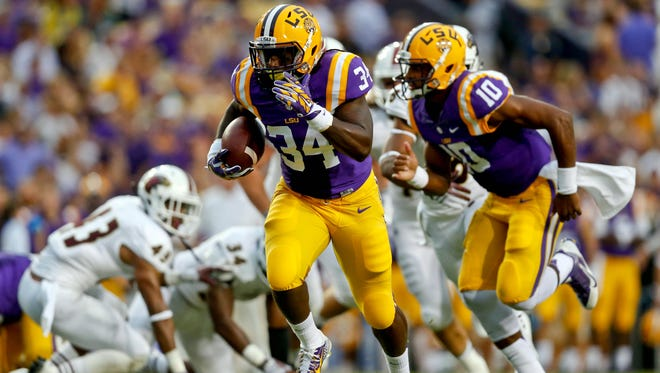 LSU Tigers running back Darrel Williams (34) runs for a touchdown against the Louisiana Monroe Warhawks during the first half of a game at Tiger Stadium.