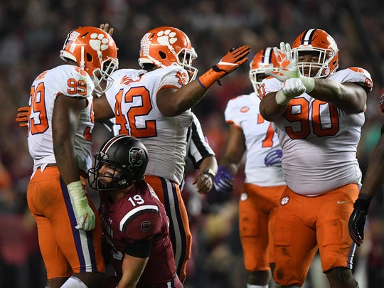 From left, Clemson defensive lineman Clelin Ferrell (99), defensive lineman Christian Wilkins (42), and defensive lineman Dexter Lawrence (90) react after a sack of South Carolina quarterback Jake Bentley (19) during the 2nd quarter on Saturday, November 25, 2017 at Carolina's Williams Brice Stadium.